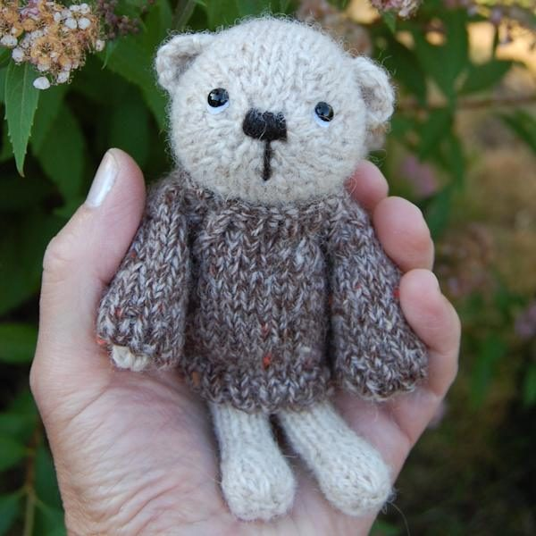 Little Malcolm, a hand knitted pocket size teddy bear made using pure soft alpaca wool.