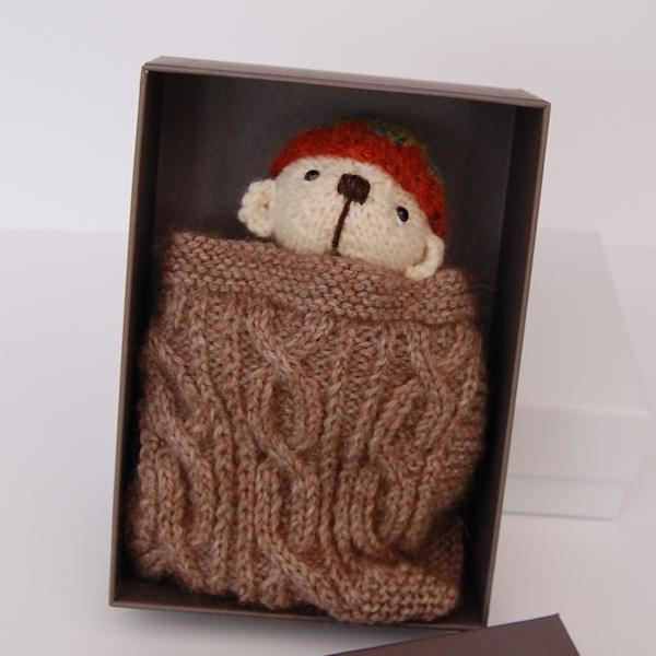 The very cute Twigglet modeling our new gift box and hand knitted blanket which come with all of the Pocket Teddy Bears